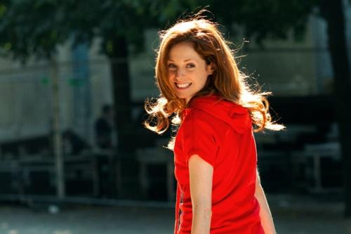 Une russe en rouge avec un grand sourir sous le ciel.