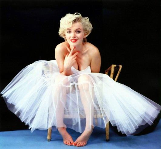 Marilyn Monroe dans une robe en tulle transparente, assise sur la chaise en pieds nus