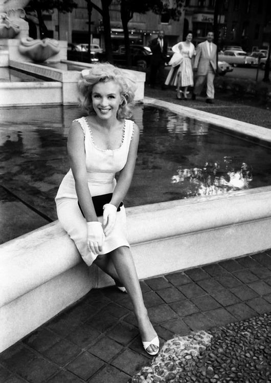 Marilyn Monroe assis à côté d'une fontaine en robe blanche