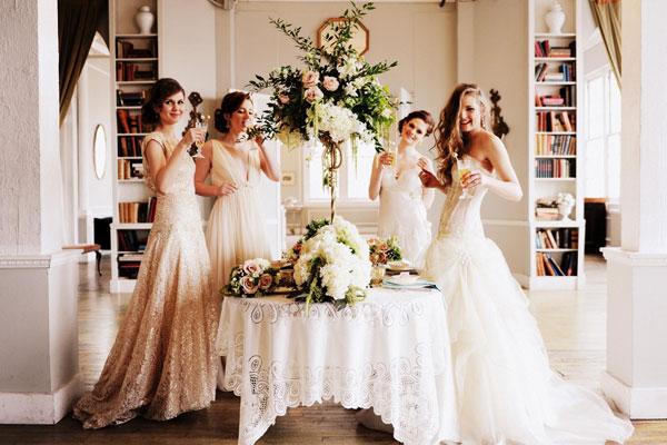 4 mariées boivent en portant des robes de mariée blanches élégante
